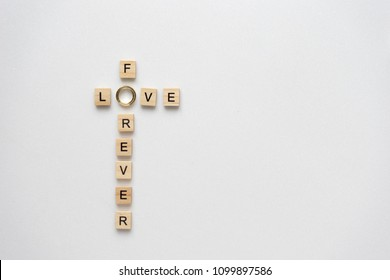Wooden letters and wedding rings spelling love for ever. Top view.