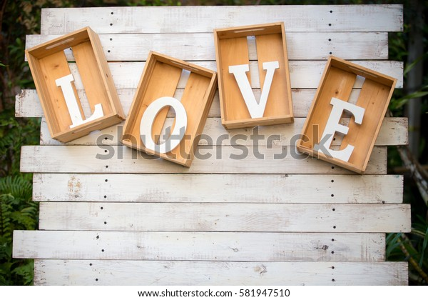 Wooden letters word LOVE in wooden box, hanging on brick wall background, can be use to background, wallpaper, greeting card, template and screensaver. Love anniversary concept and signature.