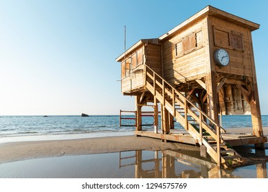 A wooden lifeguard watch hut with a clock on the beach in Tel Aviv, Israel
