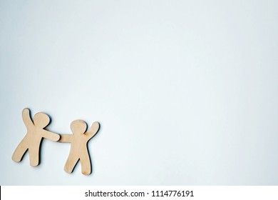Wooden little men holding hands with blank white space for text or logo. Symbol of friendship, love and teamwork