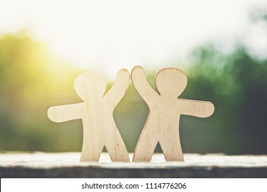 Wooden little men holding hands on natural sunlight background. Symbol of friendship, love and teamwork