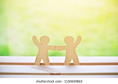 Wooden little men holding hands. Symbol of friendship, love and teamwork