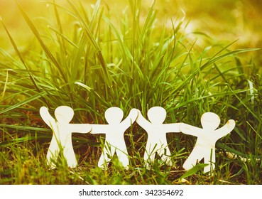 Wooden little men holding hands in summer grass. Symbol of friendship, family, teamwork or ecology concept