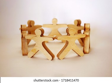 Wooden little men stand in the circle and hold hands together on the white background