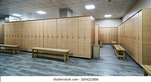 Wooden lockers with a wood bench in a locker room with doors closed. Locker room interior in modern fitness gym