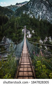 Wooden long footbridge above the deep gorge with a river at the bottom, between the rocks. Wild mountains in Swiss Alps - bridge in Switzerland