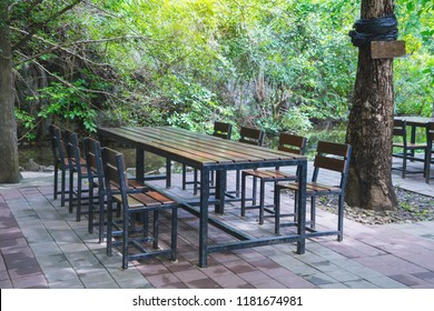 Wooden long table and bench under tree shade, natural garden seat idea. Restuarant, outdoor public park.