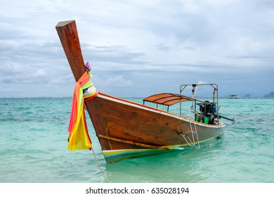 Wooden long tail boat anchored on turquoise sea, krabi, thailand