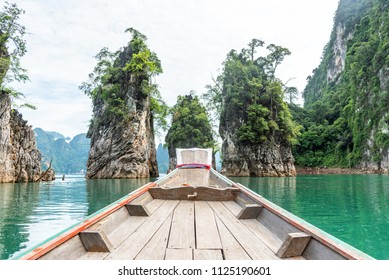 Wooden long-tail boat with rock mountain and lake in Ratchaprapa dam, Khoa Sok National Park, Surat Thani, Thailand.