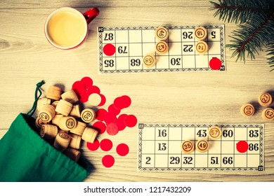 Wooden lotto barrels with bag, game cards, red chips and cup of coffee