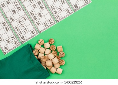 Wooden lotto barrels with cloth bag and game cards on green background. Board game lotto. Top view with copy space.