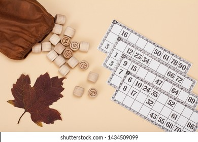 Wooden lotto barrels with open bag, dry autumn leaf and game cards on beige background. Board game lotto. Top view.