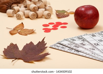 Wooden lotto barrels with open bag, dry autumn leaf, red apple and game cards on beige background. Board game lotto.