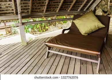 Wooden lounge chair with brown and green cushions on top of a timber deck with a thatched roof covering.