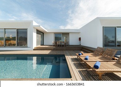 Wooden lounge chairs in modern villa pool and deck