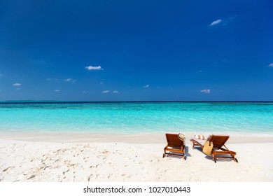Wooden lounge chairs on a beautiful tropical beach at Maldives
