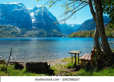 Wooden love seat for two on the shore of a lake on summer afternoon. Hallstatt, Austria