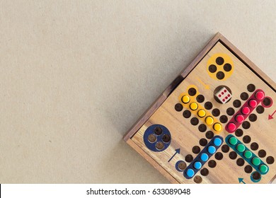 Wooden Ludo on Brown Paper Background. Copy Space for Text.