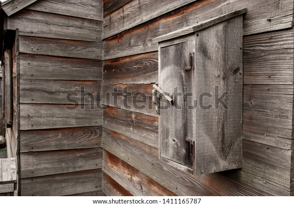A Wooden Mailbox on a rustic vintage wood cabin that is weathered and grungy.