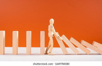 Wooden man stopping falling domino concept. Symbol of crisis, risk, management, leadership and determination. Domino effect. Fall of the crumbling business is saved by mannequin. Orange background.