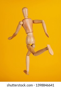 Wooden man toy running back view isolated on yellow background