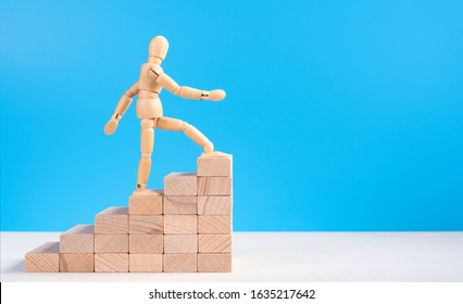 Wooden man walk up the career stairs. Ladder made with wooden bricks. Mannequin on top of development. Concept of personal development, career , changes, success. Blue background, copy space for ad
