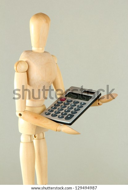 Wooden mannequin with calculator on grey background