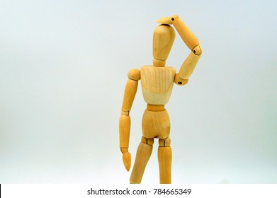 Wooden mannequin figure hand to head - body language bad idea. Oops.