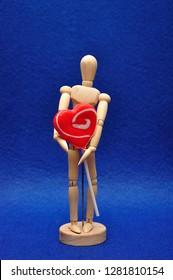 A wooden mannequin holding a heart shape lollipop