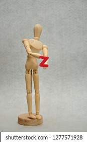 A wooden mannequin holding a letter z