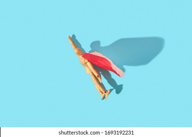 Wooden mannequin miniature doll in a red cape with raised hand flies up as hero on a light blue background, copy space. Business success and leadeship concept.