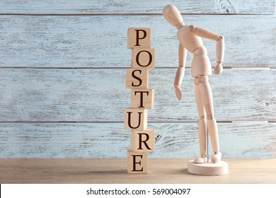 Wooden mannequin near tower of cubes with word POSTURE on table against light background