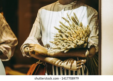 Wooden mannequin in a showcase wearing a shirt and bunch of wheat in his arms