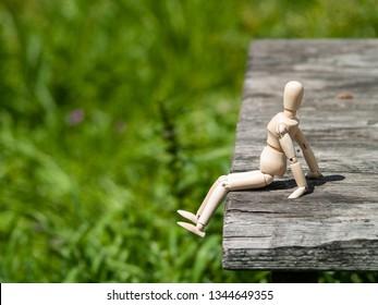 A wooden mannequin sitting on a wooden board taking a sunbath