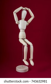 a wooden mannequin in sitting position with the hands on the head and with a red background
