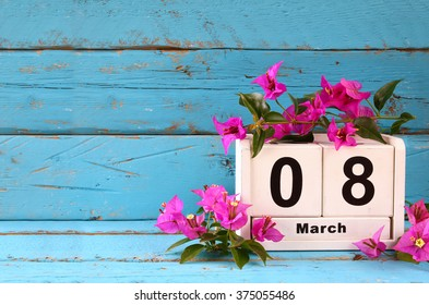 wooden March 8 calendar, next to purple flowers on old blue rustic table. selective focus