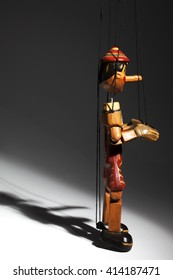 Wooden marionette of Pinocchio liar with big nose. Dramatic light.