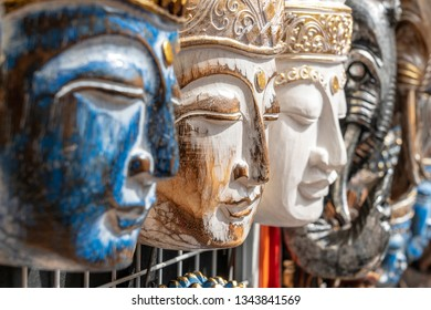 Wooden mask with the image of the Buddha on display for sale on street market in Ubud, Bali, Indonesia. Handicrafts and souvenir shop display, close up