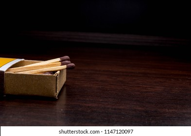 Wooden match on wooden desk background. Selective focus.