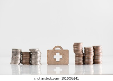 wooden medicine bag model and coin stack illustrate financial saving, health insurance concept