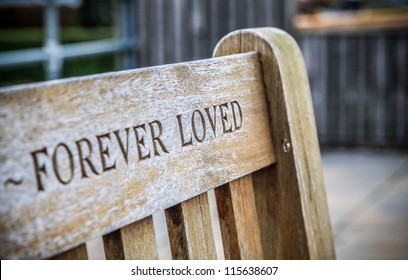 Wooden memorial bench with FOREVER LOVED carved into the back of it