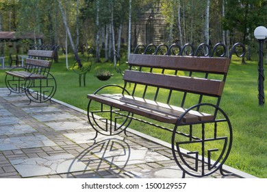 Wooden and metall bench in beutiful place among the grass in park
