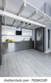 Wooden mezzanine over modern kitchen with bright wood floor