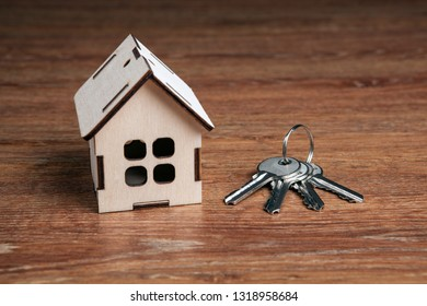 wooden miniature house and a door key on a wooden background close up