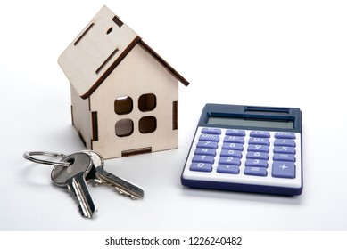 wooden miniature house with door keys and a calculator close up