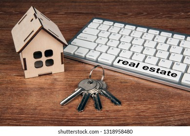 wooden miniature house with door keys and a pc keyboard close up