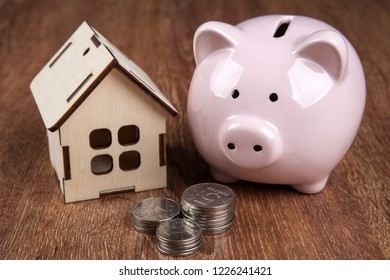 wooden miniature house and pink piggy bank with Russian ruble coins close up