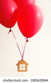 Wooden miniature house in red balloons on a light background. Conceptual image of acquisition of housing