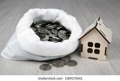wooden miniature house with Russian ruble coins in the white bag close up