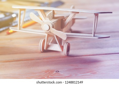 Wooden model airplane and tools on wood on wooden boards, home creativity concept, copy space
